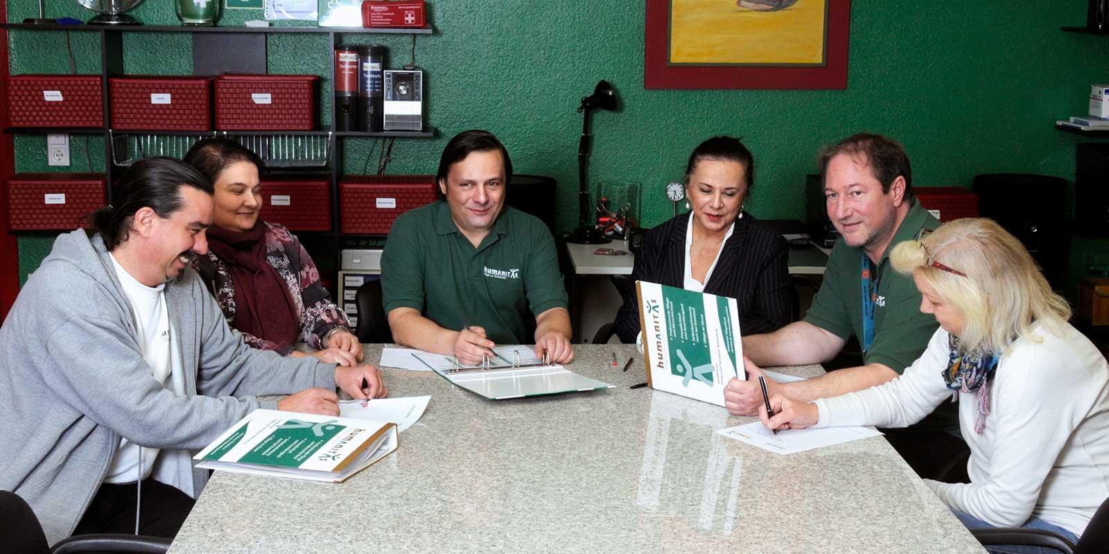 Das Humanitas-Team sitzt bei einer Besprechung gemeinsam zusammen am Tisch